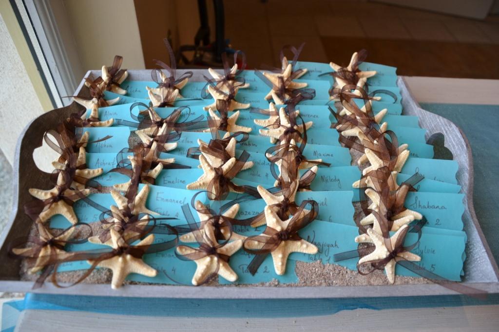 Escort cards DIY attachées à des étoiles de mer, ruban organza chocolat, turquoise, sable